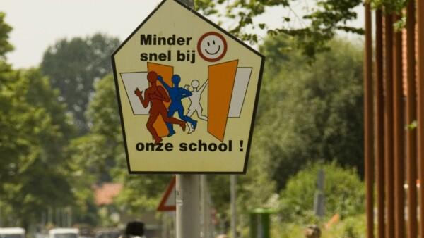 Afbeelding van verkeersbord dat aanmoedigt vaart te minderen bij school