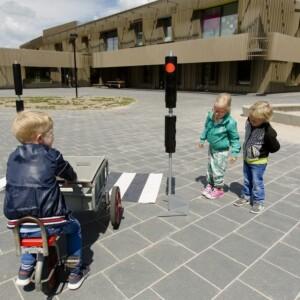 Kinderen oefenen op plein met verkeerssituaties