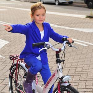 Jong meisje op fiets steekt haar hand uit om richting aan te geven